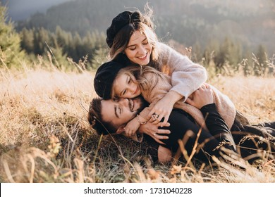 Stylish young family in the autumn mountains. A guy and a girl with their daughter lie and cuddle on the grass against the background of the forest and mountain peaks at sunset.
