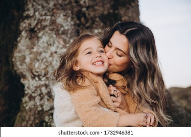 Stylish young family in the autumn mountains. Mom and daughter are sitting under a large old tree and hugging against the background of the forest and mountain peaks at sunset.