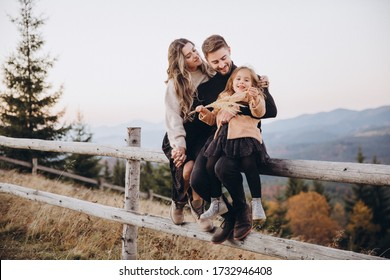 Stylish young family in the autumn mountains. A guy and a girl, together with their daughter, are sitting on a fence amid a forest and mountain peaks at sunset.