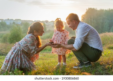 stylish young Family of mom, dad and daughter one year old blonde sitting near father on shoulders, outdoors outside the city in a park amid trees in summer. Wear jeans clothes. Family photo session.