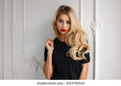 Stylish young fashionable blond woman with a hairdo in a trendy black t-shirt near a white vintage wall