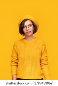 Stylish young female in glasses and beret looking at camera with raised eyebrow and being sceptical against yellow background