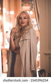 Stylish young girl 20-24 year old wearing beige elegant dress and autumn jacket posing in cafe closeup. Looking at camera.