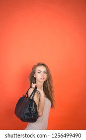 stylish young girl with a black bag on a red background