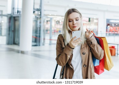 stylish young girl concetrate on the phone with shopping bags. Brown raincoat. concept: shopping, sales, Consumerism, lifestyle
