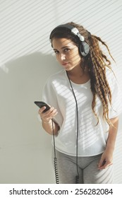 Stylish young girl in headphones listening to the music and looking at the camera