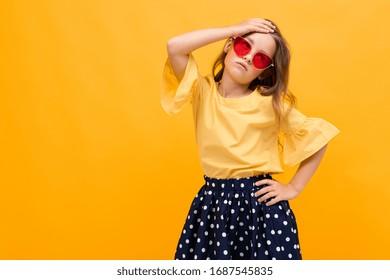 stylish young girl posing isolated on a yellow studio background