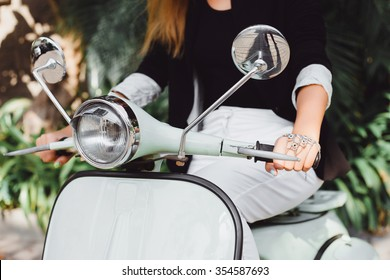 Stylish young girl sitting behind the wheel scooter retro colors Tiffany in black jacket Italian fashion and style atmosphere Europe