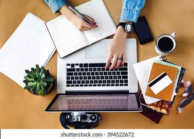 stylish young girl working  analytics holding pen on craft background with laptop and papers flat lay