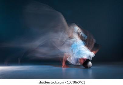 Stylish young guy breakdancer dancing hip-hop on the floor in neon light. Dance school poster. Long exposure shot