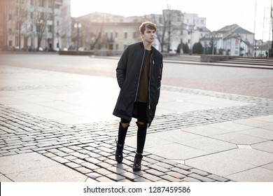 Stylish young hipster man in a fashionable black long jacket in ripped stylish jeans in a T-shirt in trendy sneakers in stylish glasses posing in the city on the street. Attractive modern guy.