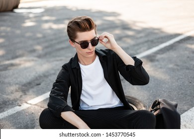Stylish young hipster man in trendy sunglasses in an elegant shirt in striped pants resting on a sunny day outdoors. Handsome guy model enjoys sunny summer day sitting on the asphalt in the city.