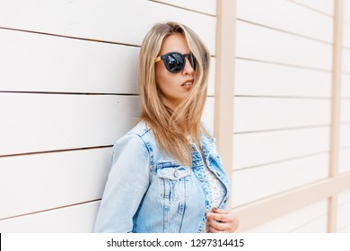 Stylish young hipster woman in black sunglasses in trendy denim blue jacket posing near a wooden vintage white building outdoors on a sunny summer day. Modern cute girl.
