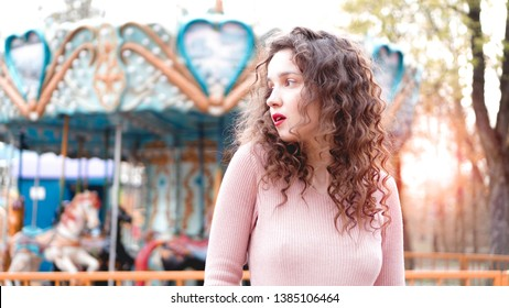 Stylish young hipster woman posing outdoors on the background of carousels. Girl enjoys a summer day