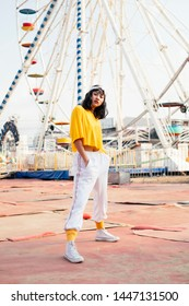 Stylish young hipster woman in stylish in a trendy yellow t-shirt posing outdoors on the background of carousels. Asian girl enjoys a bright summer sunset.