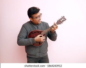 an stylish young indian musician with spectacles in black dress playing mandolin in a happy mood. Man playing guitar and smiling with copy space - Shutterstock ID 1864243912