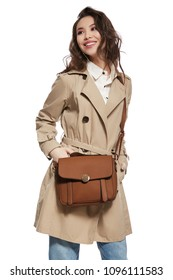 A stylish young lady in a trench coat and denim pants, a brown bag slung over her shoulder. The pretty girl standing on the white background, hands in pockets, looking aside with a smile on her face.