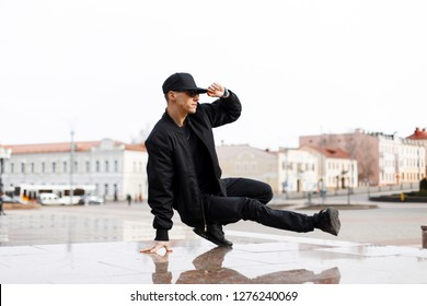 Stylish young male dancer in fashionable black clothes dancing blake dance on a street in the city on an autumn afternoon. Lifestyle.