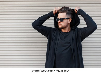 Stylish young man with a beard in sunglasses in a black hoody dresses a hood near a metal wall