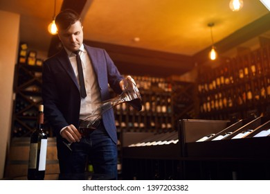 stylish young man in blue suit and white shirt pouring wine from decanter to the glass. close up photo.copy space. passion for wine