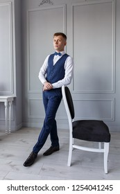 Stylish young man in a business suit a guy in trousers and a vest on a light background stylish  grooms morning  in the hotel room a man in a shirt and trousers on a chair