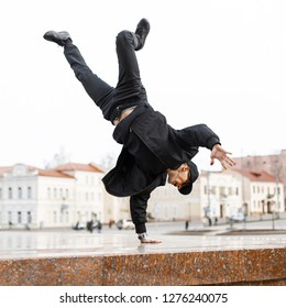 Stylish young man dancer in black jeans in a stylish jacket in a cap in sunglasses does a handstand in the city on the street. American hipster guy.
