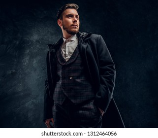 A stylish young man dressed in an elegant suit and coat posing with a hand in a pocket against a dark textured wall