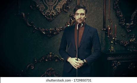 Stylish young man in elegant classic suit stands with a walking stick in a luxurious vintage interior. Men's fashion.
