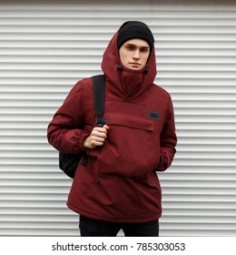 stylish young man in a fashionable winter red sports jacket with a cap of a white metal wall on the street