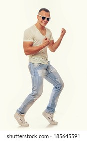 Stylish young man in glasses dancing over a white background
