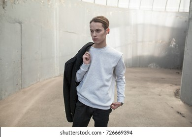 Stylish young man in gray sweatshirt on building background. Mock-up.