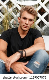 stylish young man with hair in a fashion black T-shirt and blue jeans is sitting on the beach
