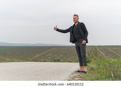Stylish young man hitchhiking in the middle of a field