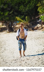 A stylish young man in jeans, a white shirt and sunglasses walking along the beach