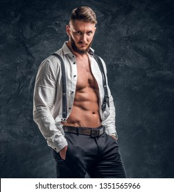 A stylish young man with a muscular body in the unbuttoned white shirt with suspenders. Studio photo against a dark wall background