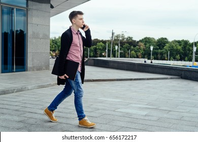 Stylish young man in plaid shirt and jeans with laptop computer  walking in the city and talking on cell phone outdoors. Student with mobile phone