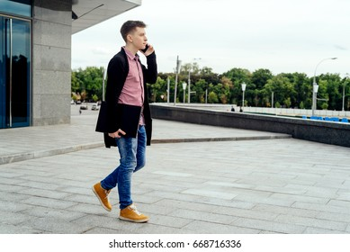 Stylish young man in plaid shirt and jeans with laptop computer in hand walking in the city and talking on cell phone outdoors, full body. Student with mobile phone
