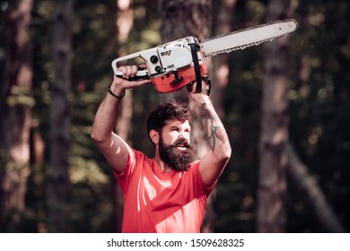 Stylish young man posing like lumberjack. Lumberjack on serious face carries chainsaw. Lumberjack worker standing in the forest with chainsaw. Man doing mans job