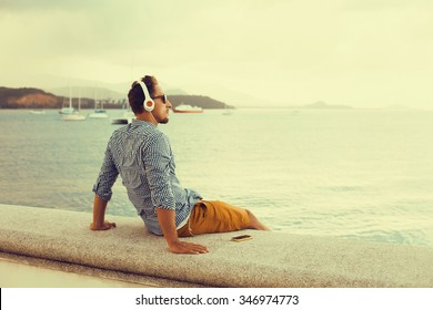 stylish young man in a shirt and shorts and sneakers listening to music in headphones on a smartphone and is sitting on pier looking at sea on yachts boats and the sunset,music lounge ,relaxing
