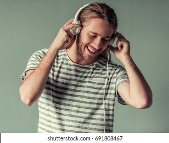 Stylish young man with shoulder-length blond hair and in headphones is listening to music and smiling, on gray background