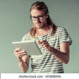 Stylish young man with shoulder-length blond hair and in eyglasses is using a digital tablet and smiling, on gray background