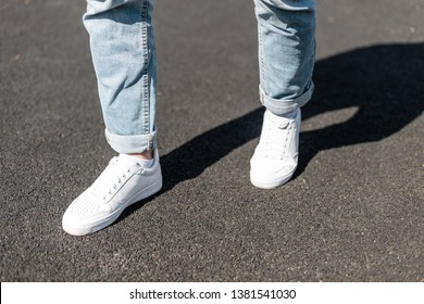 Stylish young man stands on an asphalt road in leather white sneakers in stylish blue jeans. Fashionable men's shoes. Street casual style. Close-up.