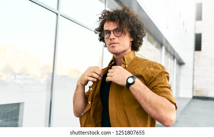 Stylish young man stundent wears shirt and wirstwatch walking on the street. Handsome male posing for advertisement with copy space outdoor in the city. People and business concept
