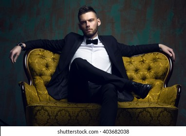 Stylish young man in a suit and bow tie. Business style. Fashionable image. Evening dress. Sexy man standing and looking at the camera. Fashion look