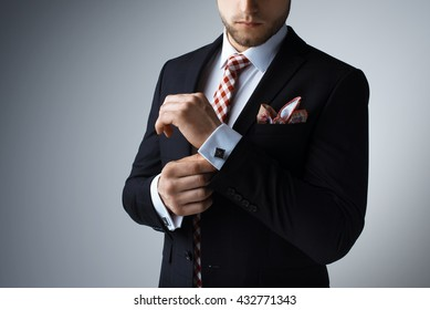 Stylish young man in suit and tie. Business style. Fashionable image. Office worker. Sexy man standing and looking at the camera. Ceremonial clothes. Secular person. Hipster look