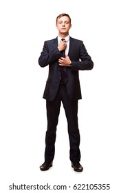 Stylish young man in suit and tie. Business style. Handsome man is standing, looking at the camera and fixing his tie