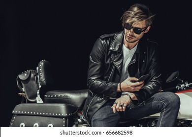 Stylish young man in sunglasses and leather jacket sitting on motorbike and using smartphone