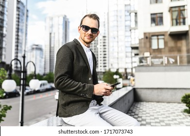 Stylish young man in sunglasses and in smart casual wear with smartphone outdoors looking at camera with smile