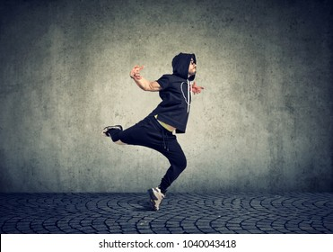 Stylish young man in trendy sportive clothing performing street dance with on gray wall background.