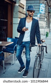 Stylish young man walking on street with bicycle using smartphone